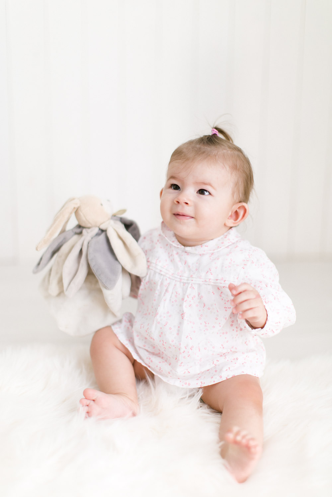 bébé tient assis avec son doudou