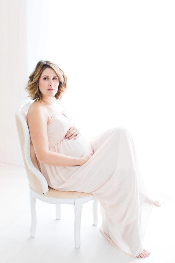 Future maman assisse avec une robe rose pastel
