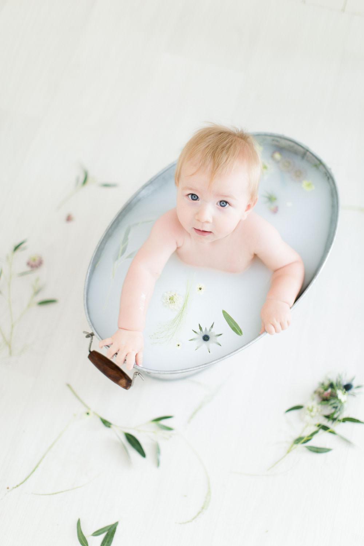 Photographie d'un bébé dans un bain de lait